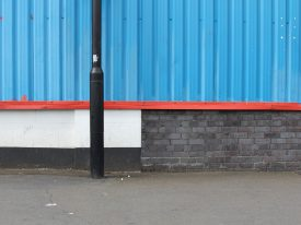 Composition in blue, red, black, white with lampost, bricks, pavement and chewing gum.